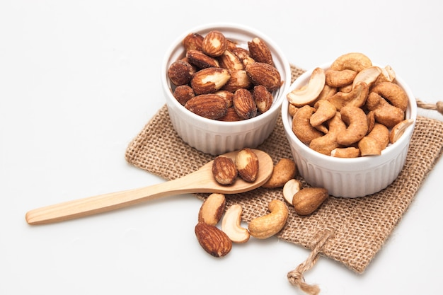 Isolate white cup of almonds nut and almonds on wood spoon