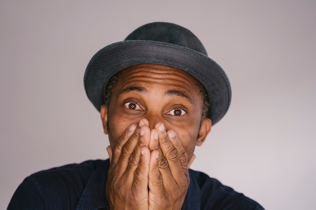 Isolated african american man covering his mouth. portrait of a man in distress about to have a panic attack.