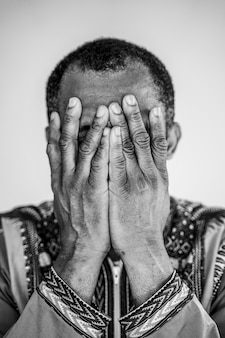 Isolated african american man covering his mouth with hands. symptoms of depression and sadness.