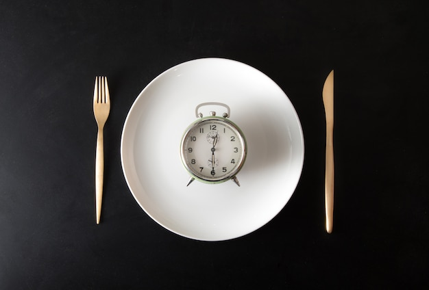 Isolated alarm clock in dish in dark