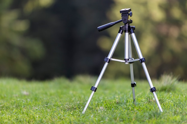 Isolated aluminum shiny tripod standing alone in fresh grassy meadow on bright sunny summer day.