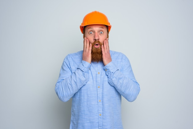あごひげとオレンジ色のヘルメットを持つ孤立した驚いた建築家