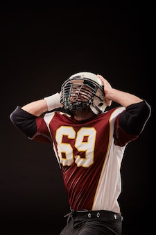 Isolated american football player rejoices in victory in black background