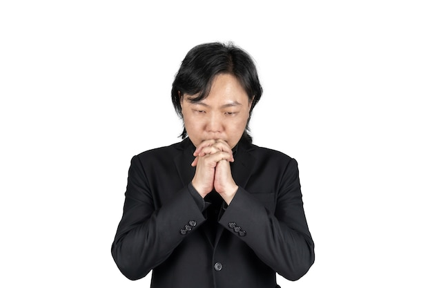 Изолированные азиатских деловой человек в черном костюме рука вместе и молится за что-то на белом фоне. обтравочный контур.
