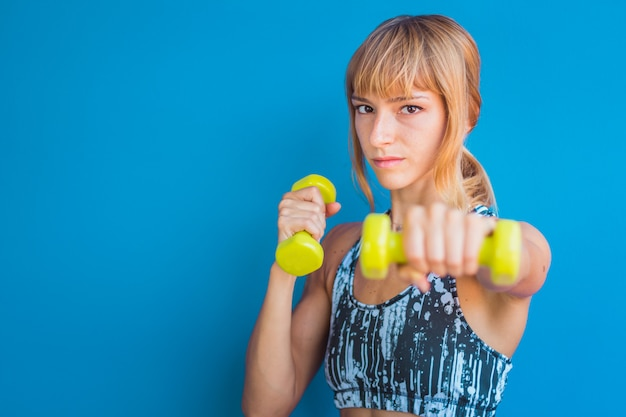 Isolated athletic young woman holding dumbbells on a blue background
