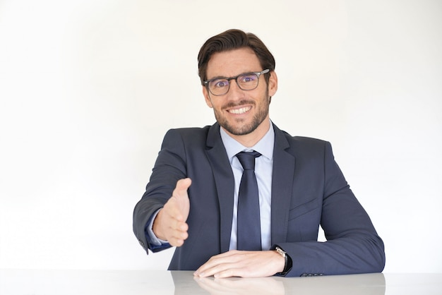 Isolated attractive businessman sitting at desk in suit with extended arm
