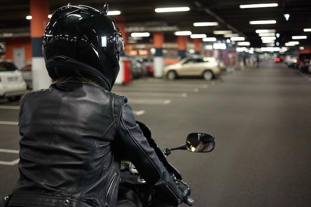 地下の舗装区画の廊下に沿って二輪のスポーツバイクを運転し、夜の乗車後にバイクを駐車する女性バイカーの孤立した背面図。モーターサイクル、エクストリームスポーツ、ライフスタイル