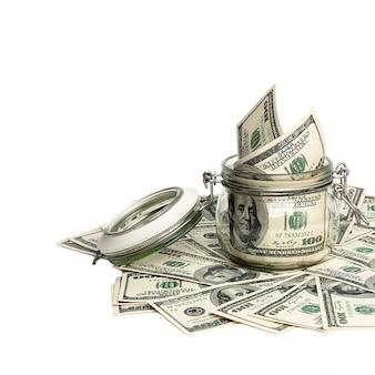 Изолированные купюры в сто американских долларов. деньги разбросаны на белом фоне вокруг банки с долларами.