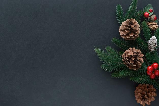Изолированный черный гранитный стол украшают сосновыми листьями, сосновыми шишками и шариками падуба в рождественской теме