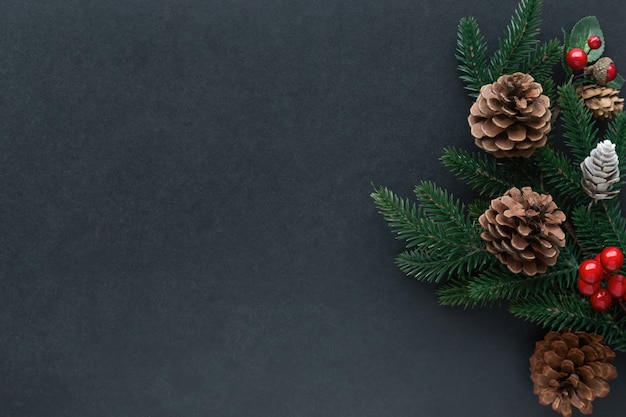 Isolated black granite table decorate with pine leaves, pine cones and holly balls in christmas theme concept