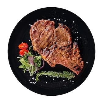 Изолированная черная тарелка жареного стейка из говядины