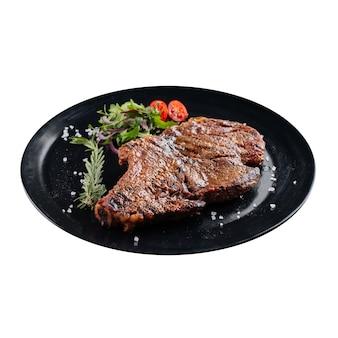 Изолированные черная тарелка жареного стейка из говядины