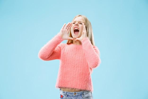Isolato su blu giovane ragazza adolescente casual gridando in studio