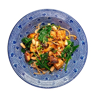 Изолированная миска азиатского блюда с лапшой тофу и вок