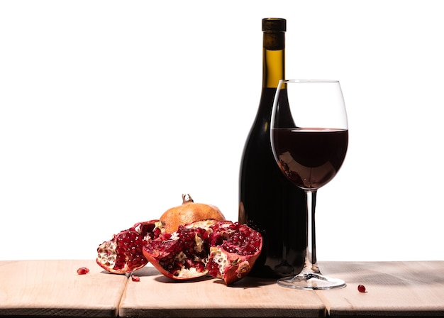 Isolated burgundy red wine bottle, wine glass and juicy pomegranate