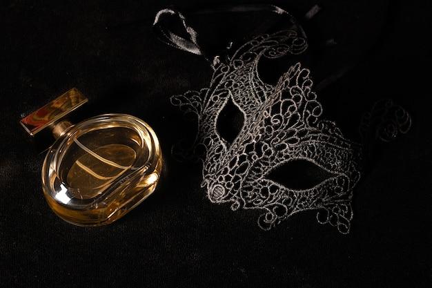 黒い表面に香水が付いた正面の孤立したカーニバルマスク