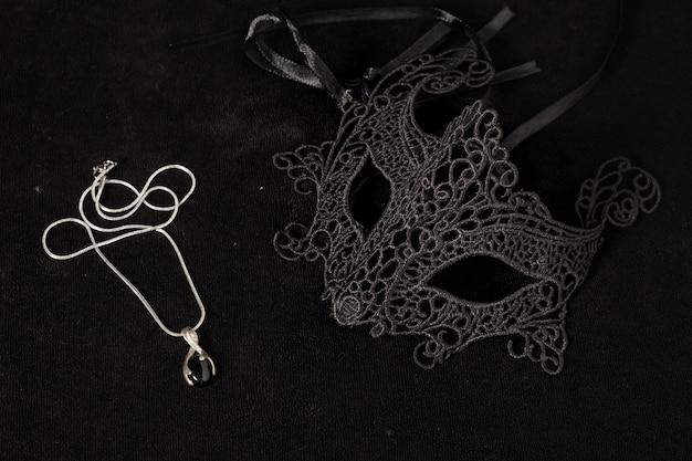 Изолированная карнавальная маска спереди с серебряным ожерельем на черной поверхности