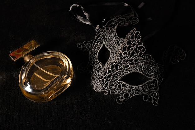 Isolated carnival mask frontal with a parfume on a black surface