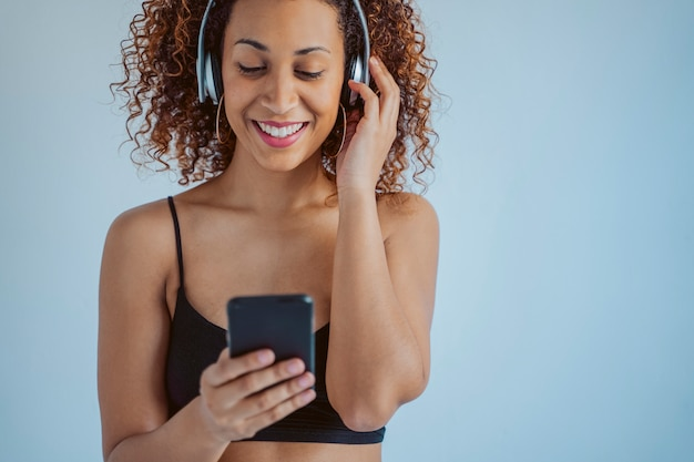 Изолированная вскользь женщина слушая к в стиле фанк музыке используя беспроволочные наушники. афрокультурный образ жизни. молодая афро-американская женщина с smartphone.