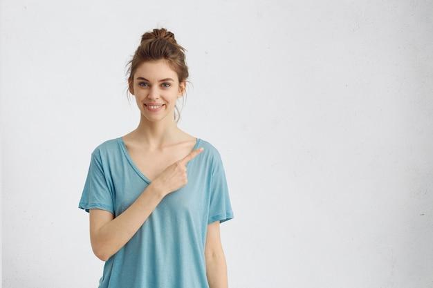 広く笑みを浮かべて、白いcopyspaceで人差し指を指しているカジュアルな青いtシャツで孤立した陽気な若い女性