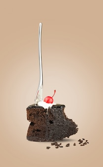Isolated chocolate cherry cake with fork from back on beige background.