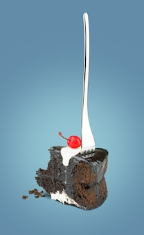 Isolated chocolate cherry cake with fork from back on blue background.