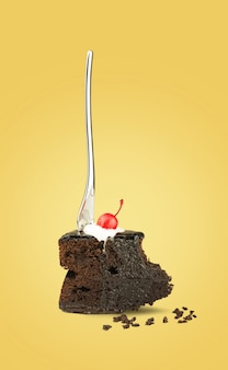 Isolated chocolate cherry cake with fork from back on yellow background.