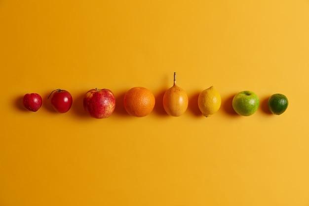 黄色の背景に並んで孤立した柑橘系の果物。グリーンライム、リンゴ、レモン、キンカン、オレンジ、フォルトゥネラ、ピーチ。あなたを健康に保つためのビタミンのホストを提供する栄養価の高いトロピカルフルーツ