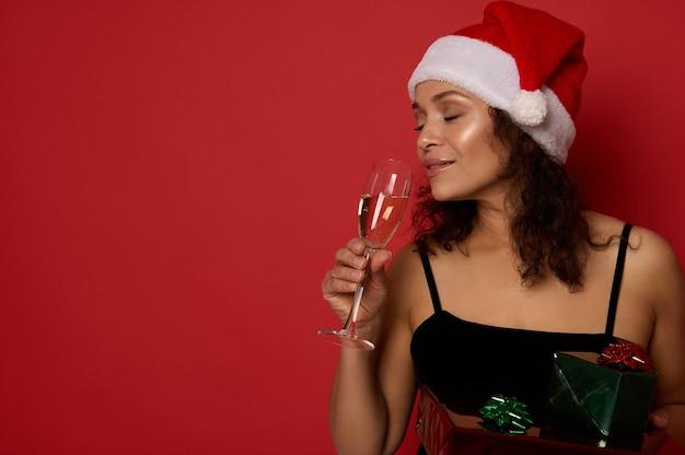 빨간 배경에 격리된 클로즈업 초상화, 저녁 화장을 하고, 산타 모자를 쓰고, 플루트에서 스파클링 와인을 마시고, 크리스마스 선물 상자를 들고 있는 매력적인 여성의 복사 공간