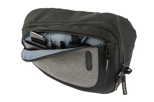 흰색 배경 앞에 지갑 스마트폰 펜 마커 배터리와 대체품을 들고 있는 프로 사진작가 블랙 카메라 가방의 전면 지퍼 구획 주머니의 스튜디오 샷을 격리했습니다.