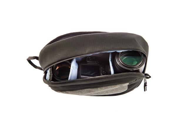 흰색 배경 앞의 부드러운 구획 안에 dslr 카메라와 렌즈를 들고 있는 전문 사진작가의 충격 방지 방수 트렌디한 블랙 패브릭 중간 배낭의 스튜디오 샷을 격리했습니다.