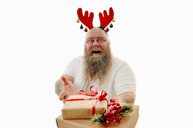 머리에 뿔과 후프를 착용 하 고 크리스마스 선물을 제시하는 문신 된 팔을 가진 overweigh 행복 한 남자의 고립 된 근접 촬영 초상화.