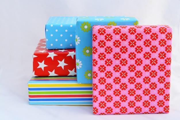 Colpo di primo piano isolato di scatole regalo in involucro colorato impilati sopra e accanto a ciascuno