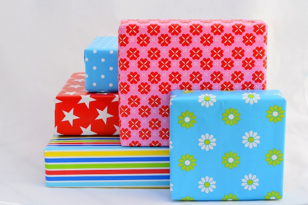 Isolated closeup shot of gift boxes in colorful wrapping stacked on top of and next to each