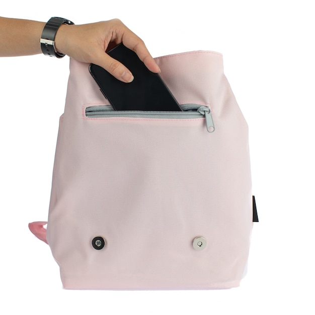 Isolated closeup studio shot of female hand putting blank screen smartphone inside front zipper pocket of small lovely stylish canvas fabric woman pink fashionable handbag on white background.
