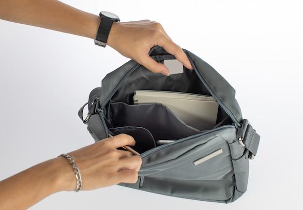 Изолированные макрофотография студия выстрел из женских рук открыть положить сенсорный планшет и ноутбук в карман отделения городской случайный серый бизнес сумочку с лебель пустой логотип на белом фоне.
