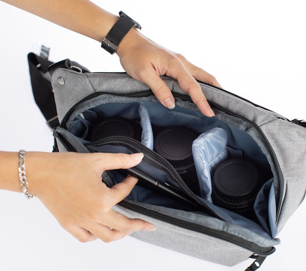 Изолированные макрофотография студия выстрел женщины-фотограф руки открыть новый многоцелевой холст ткань черный мешок камеры с противоударным карманом отделения, держа объектив и планшет внутри на белом фоне.