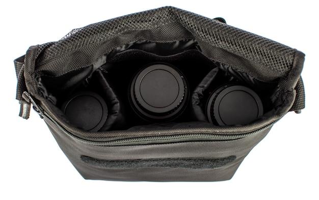 Изолированные крупным планом студийный снимок новой небольшой случайной рабочей камеры через плечо холст сумка с карманами отделения и ремешок на липучке для фотографа с тремя объективами внутри перед белым фоном.