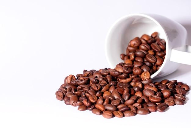 Изолированные кофейные зерна с керамической чашкой, белым столом.