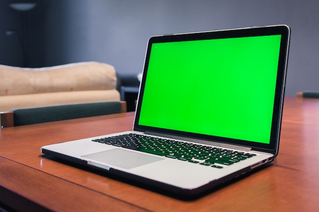 Isolated computer with green screen in a living room.