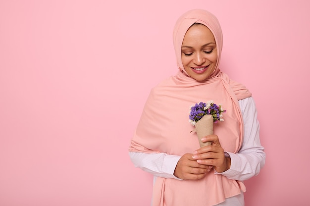 Isolated confident portrait on colored background with copy space of an attractive muslim arab woman in pink hijab, looking at a cute bouquet of wildflowers in purple shades, wrapped in craft paper