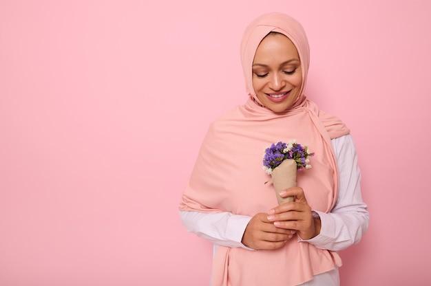 분홍색 히잡을 쓴 매력적인 이슬람 아랍 여성의 복사 공간이 있는 채색된 배경에 고립된 자신감 있는 초상화, 공예 종이에 싸인 보라색 음영의 귀여운 야생화 꽃다발을 바라보고 있습니다.