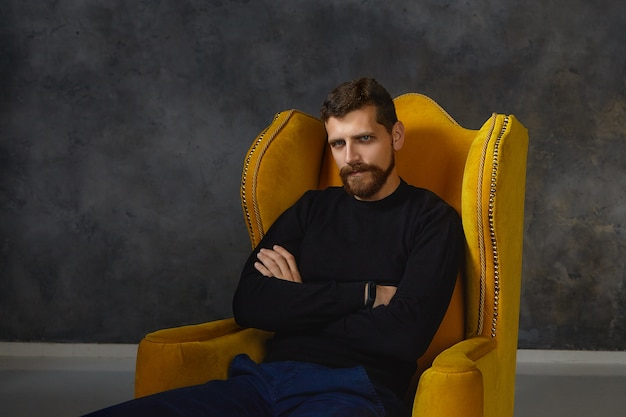 Изолированный уверенный в себе серьезный молодой человек с подстриженными усами и густой бородой сидит в желтом кресле, скрестив руки, выражая негатив, нежелание и неудовлетворенность