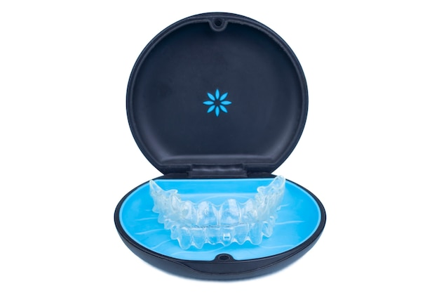 Isolated container with transparent aligner retainers or removable braces on white background