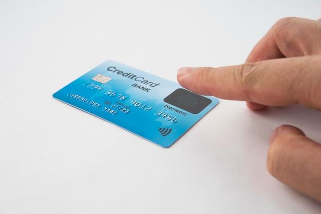 Изолированная кредитная карта и мужской палец касаясь биометрического датчика. биометрическая проверка кредитной карты. при покупке пользователь должен прикасаться пальцем к датчику. сканер отпечатков пальцев. безопасная оплата.