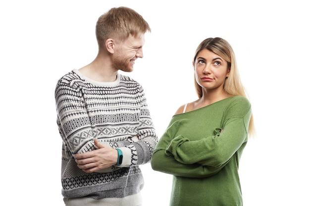 緑の長袖トップスで腕を組んで不機嫌な女の子の孤立したクロップドショット、陽気な笑顔でオタクの若いひげを生やした男と小さな話をしながら退屈を感じています。人と人間関係