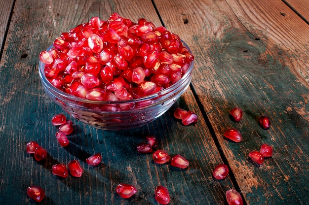 Isolated cup of pomegranate seeds on old rusty wodden board autumnal fruits antioxidants