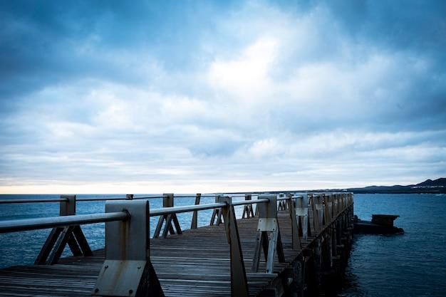 Изолированный причал без никого на нем - дождливый день и небо с облаками - пейзаж