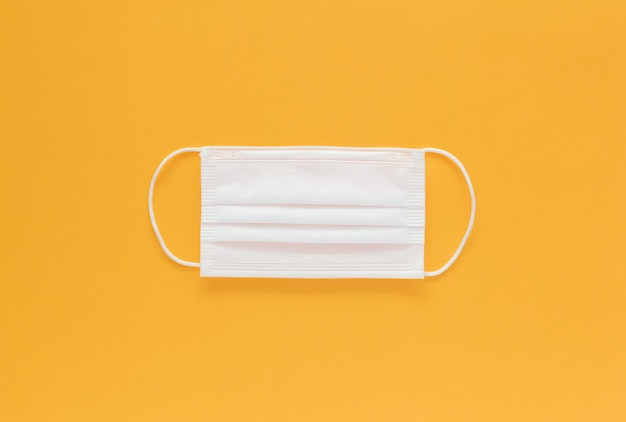 Изолированная маска для лица посередине на желтом фоне