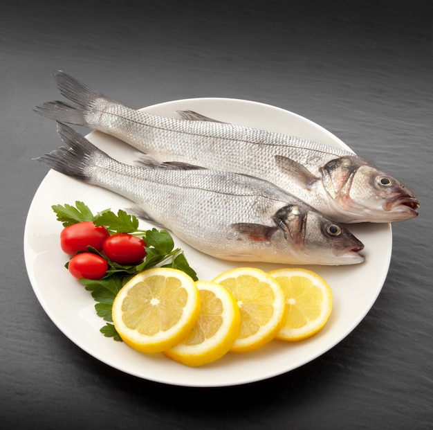 Isolated fresh bass dish in stone background